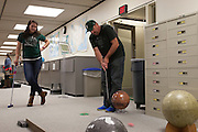Brian Wright putts a golf ball around globes while his daughter, Justine Wright looks on, during the Alden Open, a Dad's Weekend Mini-Golf event in Alden Library, on Saturday, November 7, 2015. Photo by Kaitlin Owens