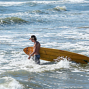 Surfer is walking into the water carrying a surfboard.