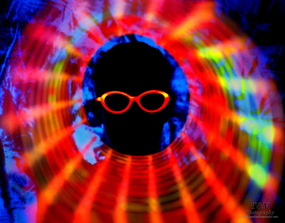 Silhouette of a boy with glowing glasses and glowing mesh in a roll.Black light