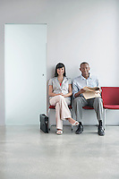 Young man and woman waiting on chairs in corridor portrait