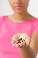 Woman holding pills, focus on hand