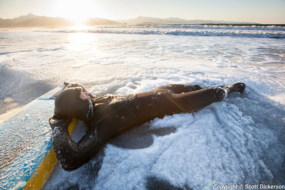 Fred Dickerson takes a rest in the slush during an icy surf session in Alaska.