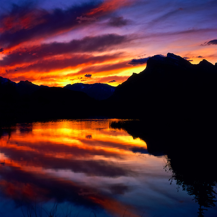 The sky is lit up as the sun rises in the First Vermillion Lake, on Banff National Park, Alberta