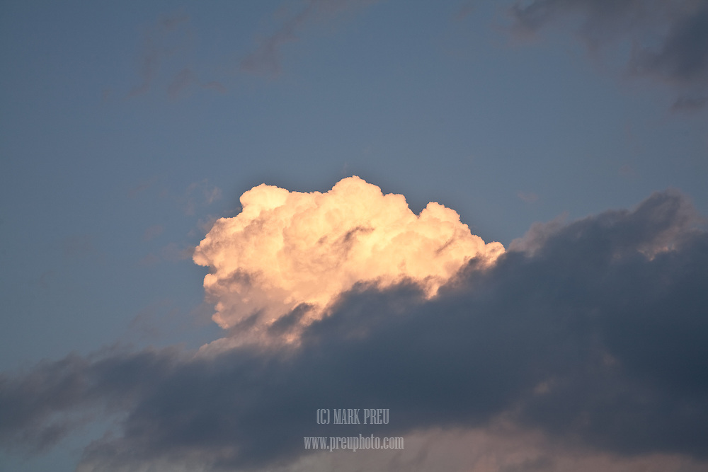 A golden cumulus cloud rises from a lower deck of gray.