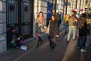 Passers-by ignore a homeless man begging with a sign saying 'I'm hungry', on the pavement in Piccadilly, on 20th January 2020, in London, England.
