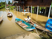 30 SEPTEMBER 2016 - SAI NOI, AYUTTHAYA, THAILAND: A flooded street that leads into Sai Noi is now a boat landing. The Chao Phraya River, the largest river that runs through central Thailand, has hit flood stage in several areas in Ayutthaya and Ang Thong provinces. Villages along the river are flooded and farms are losing their crops due to the flood. This is the same area that was devastated by floods in 2011, but the floods this year are not expected to be as severe. The floods are being fed by water released from upstream dams. The water is being released to make room for heavy rains expected in October.      PHOTO BY JACK KURTZ