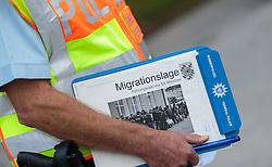 "25.09.2015, Grenzübergang, Freilassing, AUT, Fluechtlingskrise in der EU, im Bild Flüchtlinge an der Grenze zu Österreich, ein Polizist mit einem ""Migrationslage"" Dokument // Migrants on the Austrian Border, in cop with a ""migration situation"" document. Thousands of refugees fleeing violence and persecution in their own countries continue to make their way toward the EU, border crossing, Freilassing, Germany on 2015/09/25. EXPA Pictures © 2015, PhotoCredit: EXPA/ JFK"
