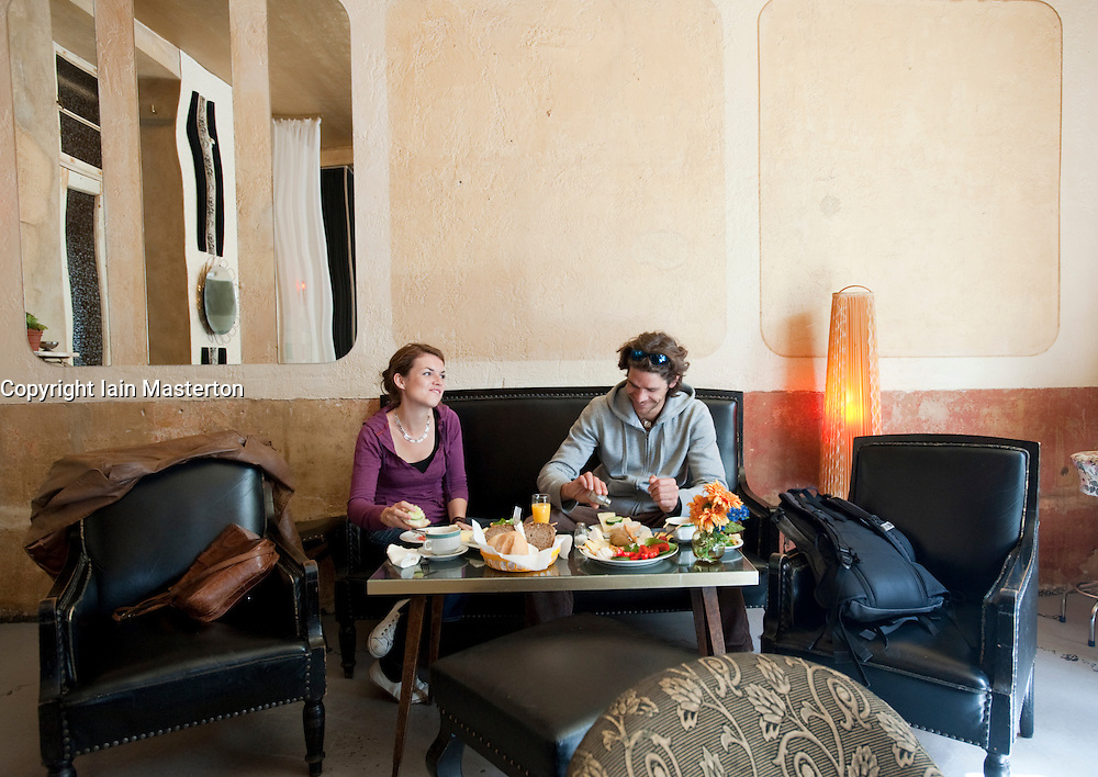 Young couple eating breakfast brunch in Wohnzimmer cafe in ...