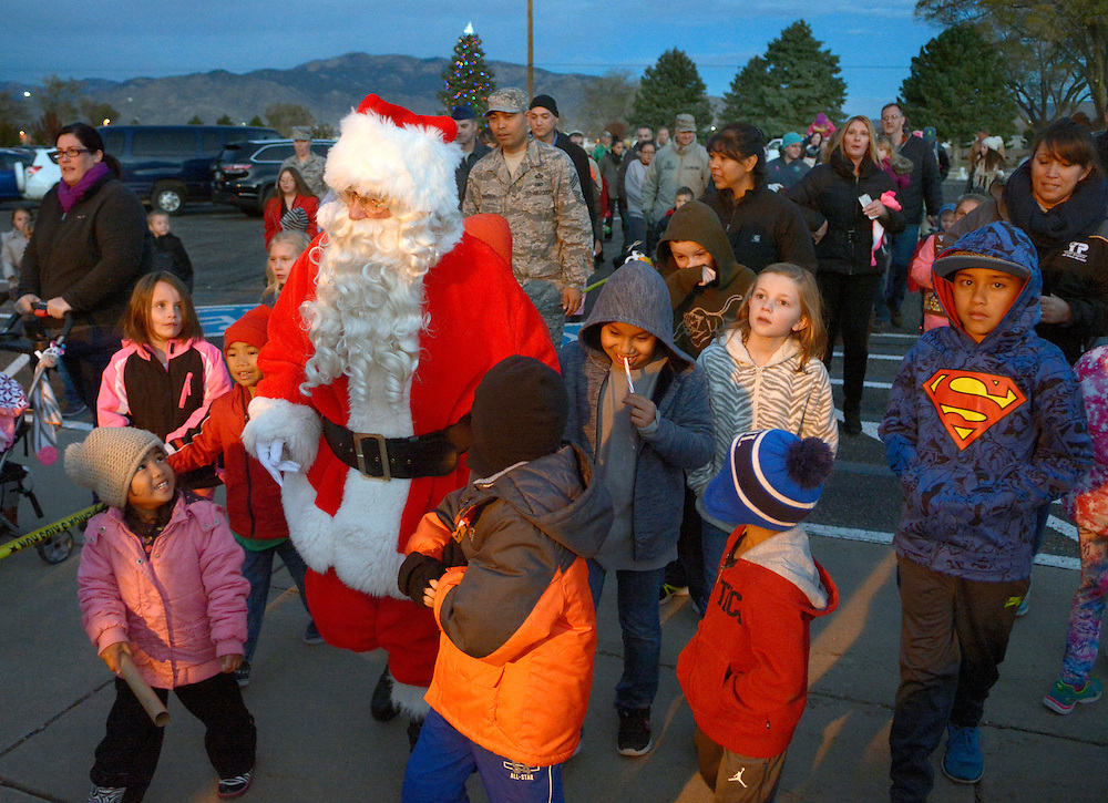 gbs120116c/ASEC -- Santa's is surrounded by children as he arrives at the Kirtland Air Force Base tree lighting ceremony on Thursday, Dec. 1, 2016. The annual ceremony features Santa Claus, caroling and refreshments.(Greg Sorber/Albuquerque Journal)