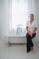 Woman sitting on edge of bathtub