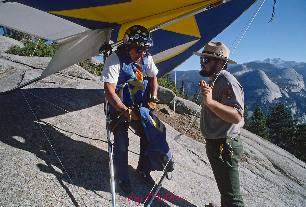Yosemite National Park ranger Roger Lockwood talks with hang glider pilot Eves Tall Chief as he prepares to launch off Glacier Point.  The sport in the park is allowed and is regulated and monitored by rangers.  July 1989.