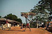 KABALA, SIERRA LEONE - A kid carries wood across a street at Kabala city on November 11, 2017 in Kabala, Sierra Leone. Photo by Xaume Olleros / MSF