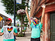 "28 JUNE 2020 - DES MOINES, IOWA: NAREN BHOJWANI and TANNER MOTE cheer during the Capitol City Pride Parade in Des Moines. Most of the Pride Month events in Des Moines were cancelled this year because of the COVID-19 pandemic, but members of the Des Moines LGBTQI community, and Capitol City Pride, the organization that coordinates Pride Month events, organized a community ""parade"" of people driving through the East Village of Des Moines displaying gay pride banners and flags. About 75 cars participated in the parade.    PHOTO BY JACK KURTZ"