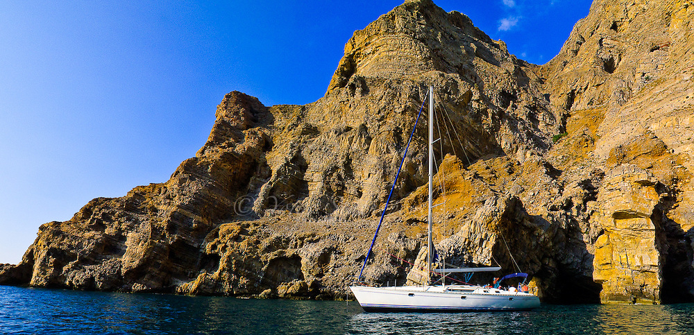 Sailboat against the mountains of Sitia, outside the village of Mochlos, Crete Greece.