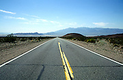 Yellow lines in straight road crossing Mojave desert between Baker and Death Valley, California, USA