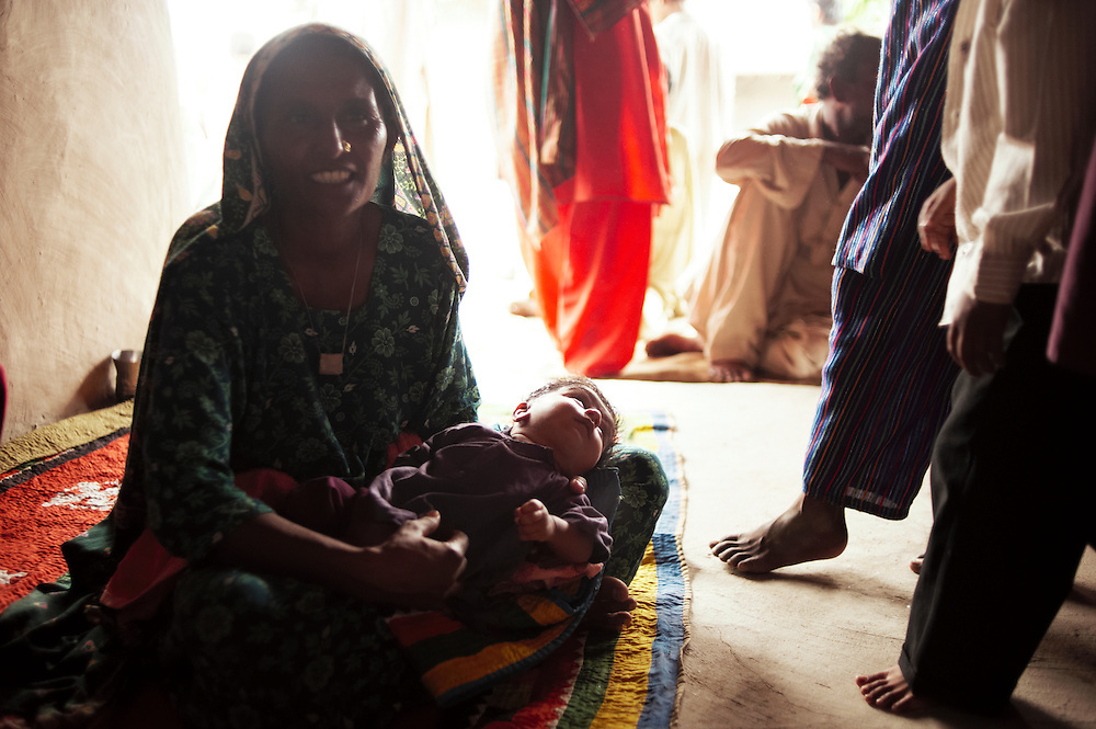 Noorojah, 38 years old holds her son Mujahid, 46 days old. and attends a class in educating better hygieneundertaken by health workers in the village of Juman Namllah, a displaced flood communitY in Badin District, Sindh, Pakistan on November 2, 2011. Health kits and education in hygiene have been conducted by Oxfam in the village. In August 2011, Heavy monsoon rains triggered flooding in lower parts of Sindh and northern parts of Punjab.