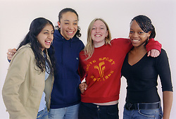 Multiracial group of teenage girls standing together smiling,