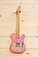 Pink paisley Fender guitar on wood grain wall
