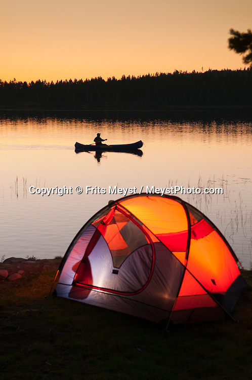 Angra, Hälsingland, Central Sweden, August 2013. A lone canoe glides through the mirror like waters of the lake, past his tent (not on the campsite). Camp Angra is a wilderness camping near Karbola owned by the Dutch Hassoldt family. Marco specialises as a wilderness guide and the camping offers Fishing and Flyfishing, Wildlifewatching, birding, outdoor fun, hiking, biking and canoeing, while Sonja runs the camping. The extensive forests dotted with hundreds of lakes of a spectacular landscape for wilderness camping. hike through the forests picking berries and collecting mushrooms, see moose and track bears and wolves. Navigate the lakes in a canoe and catch trout and salmon with a fly rod and see beavers.  Gavleborg and Dalarna regions are bursting with adventure. Photo by Frits Meyst/Adventure4ever.com
