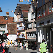 Tourists walk along street under a Tafeen, or hanging sign, above doorway of shop on the Hauptgasse, or main street, Appenzell, Switzerland<br />