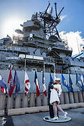 """Beside the USS Missouri at Pearl Harbor, """"Embracing Peace"""" (by sculptor Seward Johnson) recalls the iconic Alfred Eisenstaedt photograph, """"V-J Day in Times Square,"""" of a US Navy sailor kissing a stranger in New York City's Times Square on Victory over Japan Day (August 14, 1945). The photo was published in Life magazine with the caption, """"In New York's Times Square a white-clad girl clutches her purse and skirt as an uninhibited sailor plants his lips squarely on hers."""" Ordered in 1940 and active in June 1944, the USS Missouri (""""Mighty Mo"""") was the last battleship commissioned by the United States. She is best remembered as the site of the surrender of the Empire of Japan which ended World War II on September 2, 1945 in Tokyo Bay. In the Pacific Theater of World War II, she fought in the battles of Iwo Jima and Okinawa and shelled the Japanese home islands. She fought in the Korean War from 1950 to 1953. Decommissioned in 1955 into the United States Navy reserve fleets (the """"Mothball Fleet""""), she was reactivated and modernized in 1984 and provided fire support during Operation Desert Storm in January-February 1991. The ship was decommissioned in March 1992. In 1998, she was donated to the USS Missouri Memorial Association and became a museum at Pearl Harbor, on the island of Oahu, Hawaii, USA. For this photo's licensing options, please inquire."""