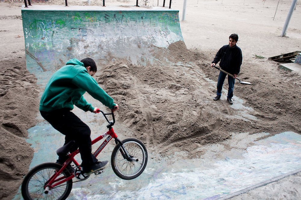 Matias Paredes (left), 15, and Alfredo Carlos Aravena, 14, remove volcanic ash from the biking ramp. They said they finally decided to ask for shovels and do it themselves because nobody else would.