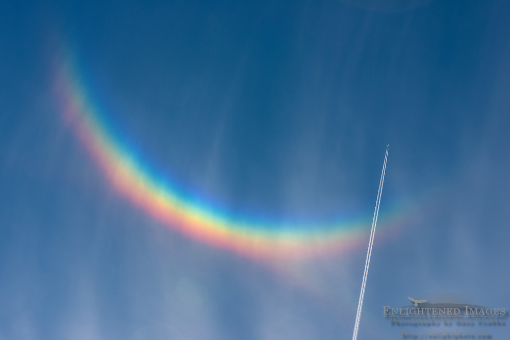 Jet airplane with contrail flying through high cirrus clouds and a circumzenithal arc