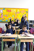 LEBANON, BEIRUT:  School classroom with children in uniforms raising their hands to volunteer answers with full bookbags by their desks.