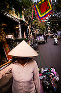 A woman walkd in Hanoi's old quarter, Vietnam, Asia