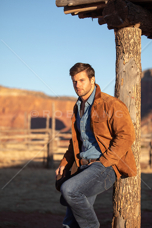 hot cowboy leaning up against a post on a ranch at sunset