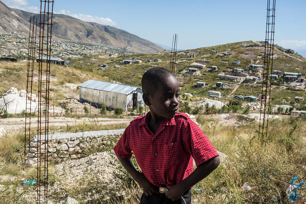 A boy in the hills at  the edge of the Corail-Cesselesse camp for people displaced by the 2010 earthquake on Sunday, December 21, 2014 in Port-au-Prince, Haiti. The camp and surrounding areas are home to tens of thousands of people, many of whom live in makeshift shacks in a barren landscape with little or no access to jobs or resources.