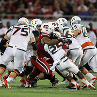Miami Hurricanes running back Dallas Crawford (25) is wrapped up during the NCAA Football Russell Athletic Bowl football game between the Louisville Cardinals and the Miami Hurricanes, at the Florida Citrus Bowl on Saturday, December 28, 2013 in Orlando, Florida. (AP Photo/Alex Menendez)