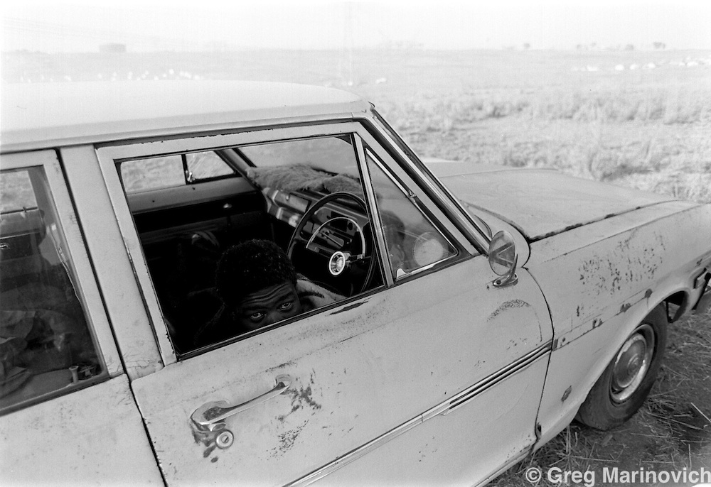 Ivory Park, South Africa, Aug 1991.  A man wakes up after spending the night in a car after police demolished the illegal shack she erected near Tembia, Transvaal, some 15km from Johannesburg. (Photo by Greg Marinovich)
