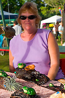 A woman sells handmade pottery frogs at the Yungaburra markets in far north Queensland.