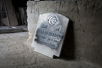 SIRACUSA, ITALY - 8 NOVEMBER 2016: A layer of fresh black paint was sprayed on the new gravestone of Musaab Shabani, a victim of the August 24th 2014 shipwreck, after being engraved by a pantograph, here at the Gibilisco marble-worker's workshop in Siracusa, Italy, on November 8th 2016. The paint in excess will later be removed by an artisan<br /> <br /> Musaab Shabani was buried in the cemetery of Sortino, marked by a gravestone with the number nine because at the time he hadn't been identified yet. He was later identified by his brother Abd thanks to the efforts of policeman Angelo Milazzo. Since then, Abd has arranged to have a gravestone made bearing his brother's name and date and place of birth as well as a religious inscription in Arabic, bringing a final bit of closure to this tragic chapter. <br /> <br /> On August 24th 2014, a boat carrying more than 400 migrants, departed from the coasts of Libya in the attempt to reach Italy, capsized in international waters in the Mediterranean Sea. Rescuers of the Italian Navy saved 352 people, and recovered 24 lifeless bodies.<br /> <br /> Following the events of the Arab Spring in 2011, including Gaddafi's death and Libya's plunge towards chaos, clandestine crossings skyrocketed, as did the number of people drowning. In 2014 over 170,000 arrived in Italy and since then more than 10,000 perished in the Mediterranean sea.<br /> <br /> Only a fraction of these bodies have ever been recovered, and, of the ones that have, the majority remain unidentified. In Sicily alone there are more than 1,500 graves of anonymous refugees and migrants–people from Syria and other war torn countries–who have drowned in shipwrecks at sea.<br /> <br /> Despite the decades long persistence of the problem, Italy has yet to develop a comprehensive approach to handling the bodies of shipwreck victims. Many pieces of a functional body identification system are in place, but its overall effectiveness is crippled by a lack of coordination between