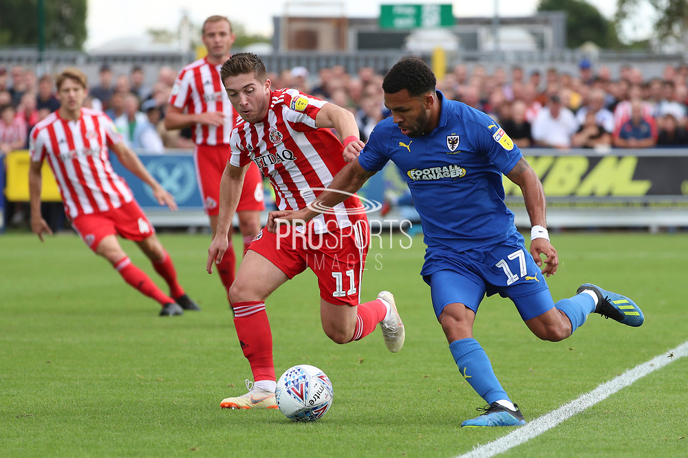 AFC Wimbledon striker Andy Barcham (17) battles for possession with Sunderland midfielder Lynden Gooch (11) during the EFL Sky Bet League 1 match between AFC Wimbledon and Sunderland at the Cherry Red Records Stadium, Kingston, England on 25 August 2018.