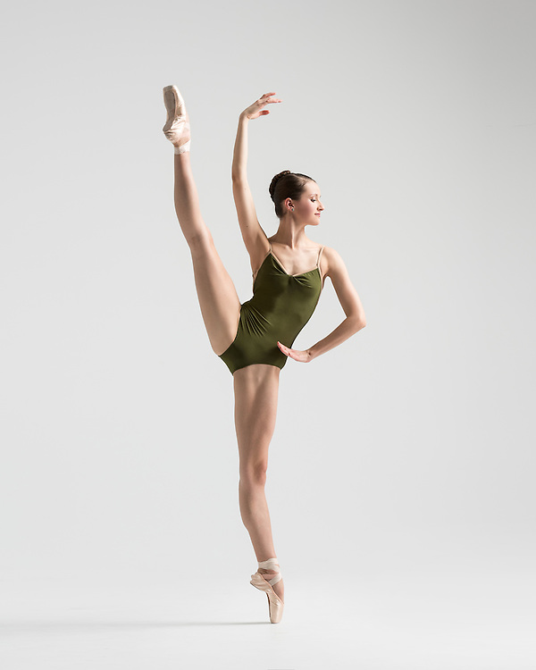 Classical ballet female dancer in a green leotard, Carly Hambridge in an a la seconde, taken in the photo studio on a light grey background. Photograph taken in New York City by photographer Rachel Neville.