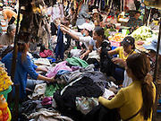 25 FEBRUARY 2015 - PHNOM PENH, CAMBODIA: Cambodian women shop for used clothing brought into Cambodia at a market in Phnom Penh.     PHOTO BY JACK KURTZ