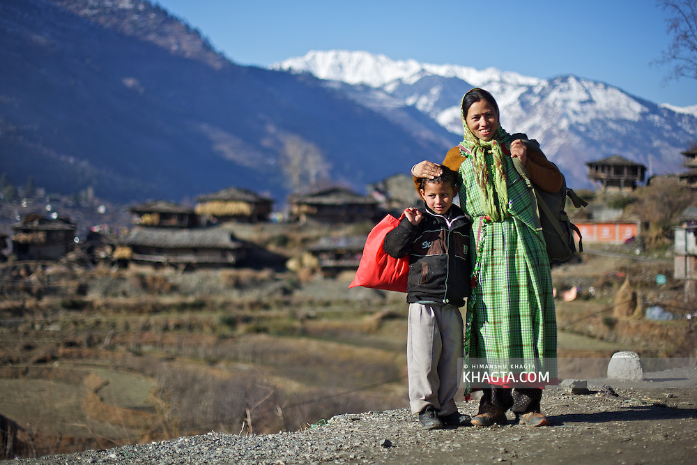 A lady dressed in Traditional Kullu attire, poses with her son at Kais Village, Kullu