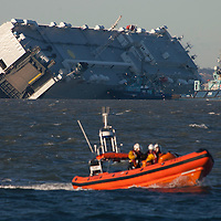 Cowes, Isle of Wight. 6th January, 2015. Life goes on in The Solent. Inshore RNLI Lifeboat stands by. Capsized car carrier Hoegh Osaka in the late afternoon sunshine. Surveyors and survey ships are in attendance to assess the state of the ship and its cargo. Windy weather is expected in the next few days. © Patrick Eden