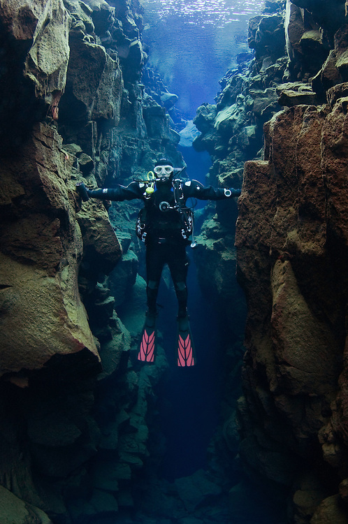 Diver reaching out between two continents, Silfra, Thingvellir lake, Thingvellir National Park, Iceland<br /> Model release by photographer