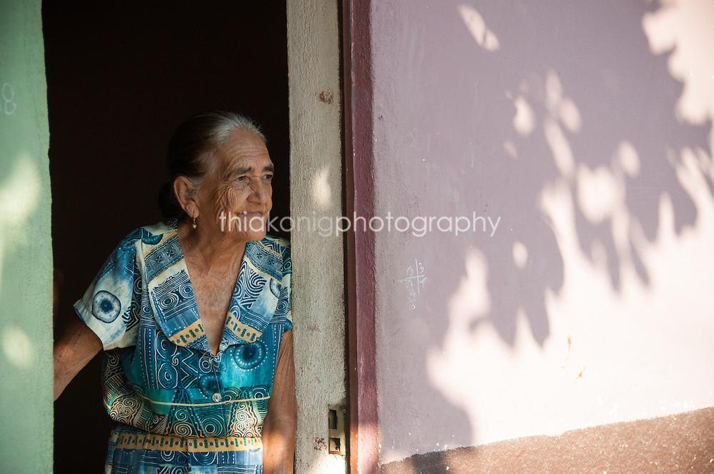 Elderly woman leans in doorway with pink wall, Barra de Navidad, Mexico