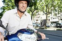 Mid-adult man riding motorscooter along city street