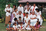 The extended Lagavale family, dressed in their Sunday best for the White Sunday holiday church services, pose for the camera in front of their house in Poutasi Village, Western Samoa. White Sunday (also called Children's Day), is celebrated on the second Sunday of October each year. In this tradition brought to the island by the London Missionary Society, the children receive new clothes and gifts, and festive games are played. Most attend church services and then gather for family feasts that feature foods like pork, taro, and coconuts. Published in Material World, pages 174-175.