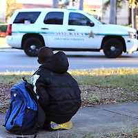 A student on his way home from school watches as law enforcement officers search for suspect Markeith Loyd at the Tzadik Brookside Apartments on January 9 2017 in Orlando, Florida. Loyd shot an Orlando Police officer earlier in the day at a local Walmart, the officer has since died.  (Alex Menendez via AP)