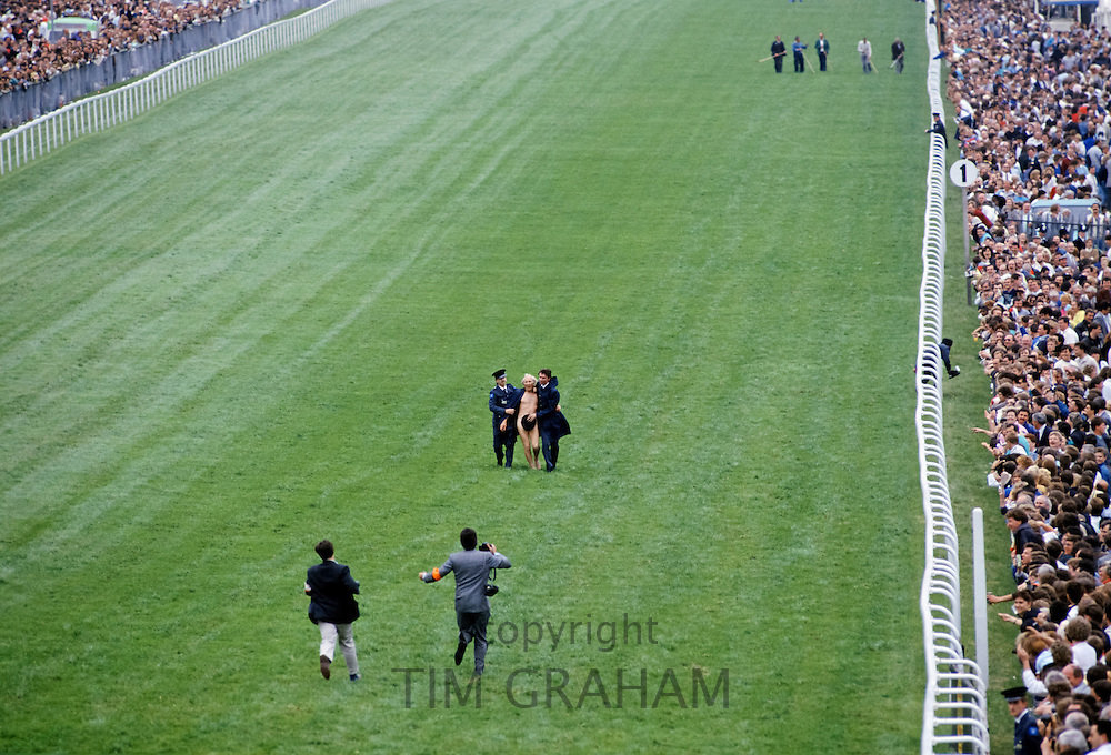 Naked streaker being led away by police after a breach of security when he ran on the racetrack at Epsom Racecourse on Derby Day, UK