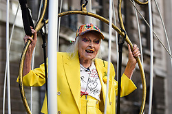 "© Licensed to London News Pictures. 21/07/2020. LONDON, UK.  Dame Vivienne Westwood re-enters public life, after being in shielding during the COVID-19 lockdown, by being harnessed into a giant birdcage and suspended 10 feet in the air in front of The Old Bailey Criminal Court in protest about the U.S. extradition trial of Julian Assange, which is to recommence at the Old Bailey on 7 September.  She is dressed in a yellow trouser suit, enacting the metaphor of 'The Canary In Coal Mine', which is indicative of ""Assange being sacrificed for identifying 'poison' in the system"".  Photo credit: Stephen Chung/LNP"