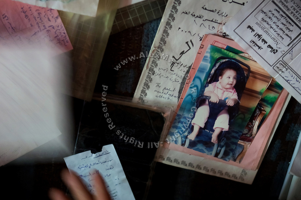 Zahra Mohammed, 5, a girl affected by a severe neurological disorder and six fingers in each hand and foot, is sitting on her pram on a family photograph, in between medical records collected by her father, in Fallujah, Iraq. The parents and their relatives have no history of birth defects.