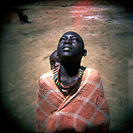 A young girl from the Toposa tribe looks up at a searing sky during a community gathering. The village lies near a former SPLA strong hold and logistics base which was heavily mined during the country's long civil war. The site is widely used for grazing and transit of animals by local residents and is much needed due to climate change caused drought in the region.<br /> Lomongole, South Sudan. 25/09/2009.