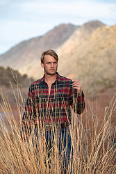man with blond hair touching tall grass
